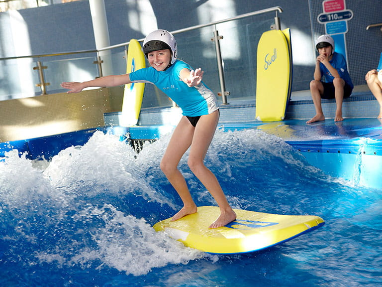 Girl surfs a wave at LC2 indoor waterpark in Swansea Bay