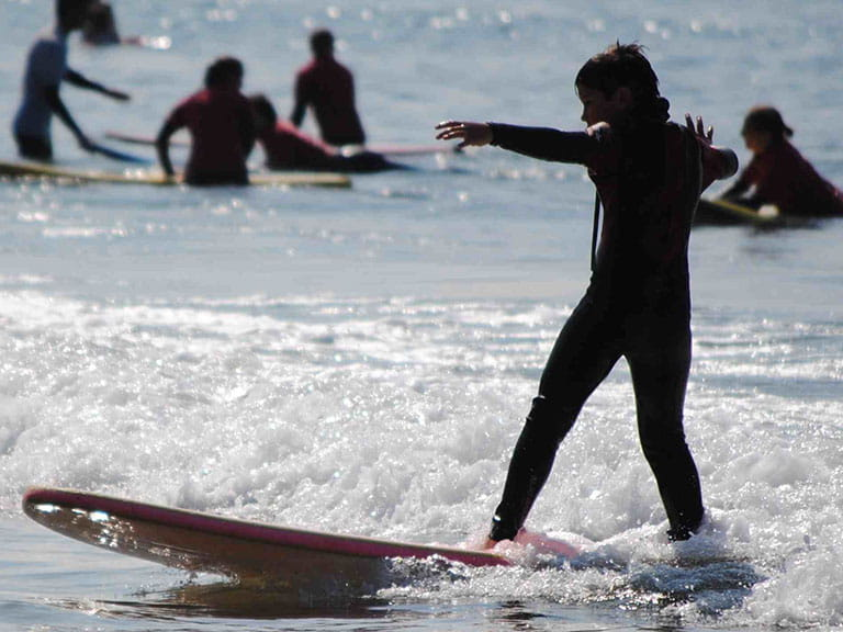 A beginner surfer rides the waves at Swansea Bay