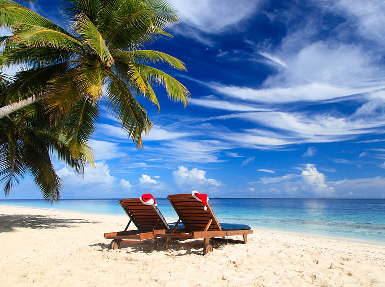 two chair lounges with red Santa hats on tropical summer beach