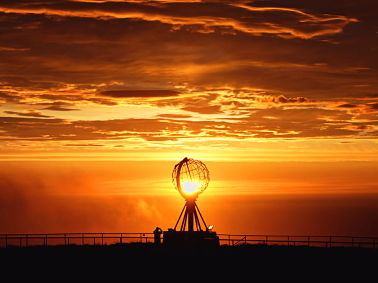 Sun setting over globe sculpture in Nord Cap