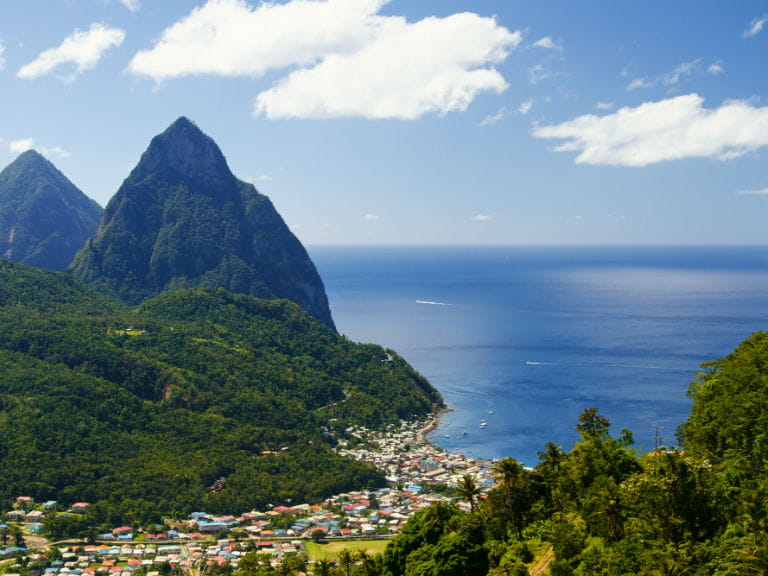 The town of Soufrière in Saint Lucia, with the Pitons, two mountainous volcanic plugs, in the background