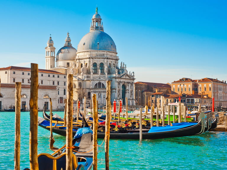 The Basilica Santa Maria della Salute in sunny weather on the azure blue Grand Canal, Venice