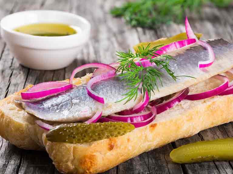 Open sandwich with herring fillets, onion, pickled cucumber and dill in Norway