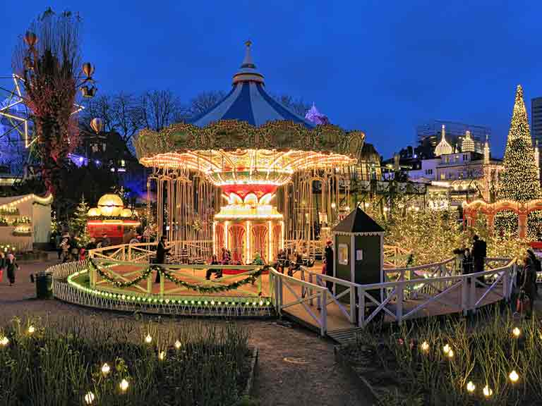 The carousel and Christmas illuminations in Tivoli Gardens, Copenhagen © Mikhail Markovskiy / Shutterstock.com S M L XL  Size Guide