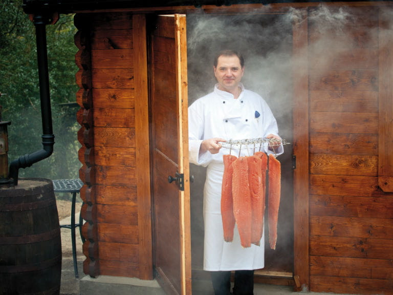 Chef holding smoked fish at the Wild Boar Inn, Cumbria
