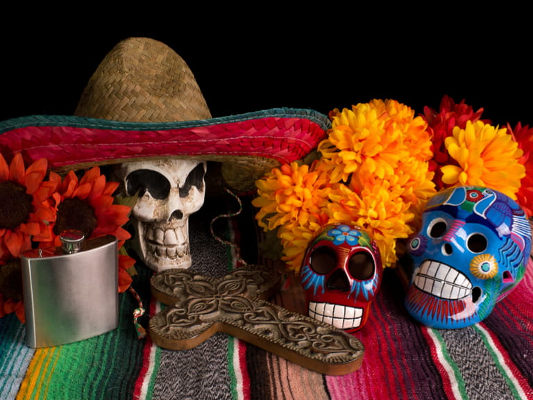 Mexican festivals represented by a traditional Dia De Los Muertos (Day of the Dead) altar/offering. With marigold & red sunflowers, colorful lumineras, decorative cross, tequila flask, & skull wearing Mexican sombreo.