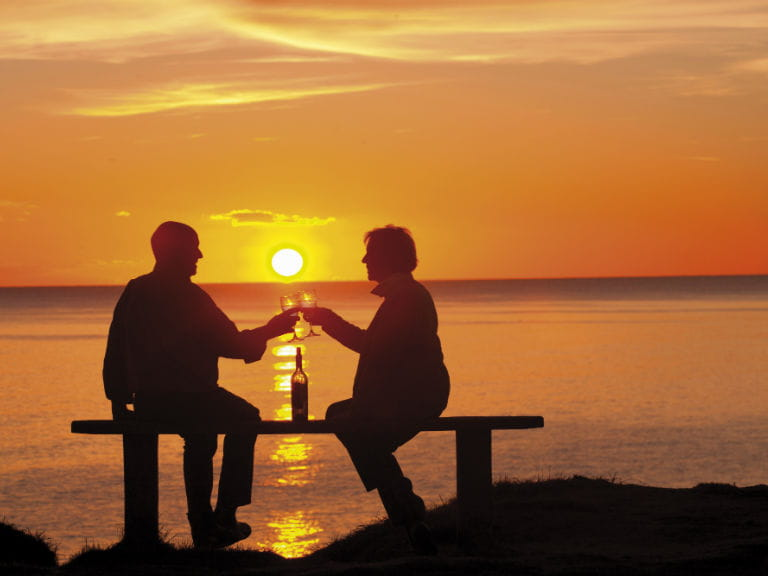 An older couple at sunset toasting against a sea backdrop