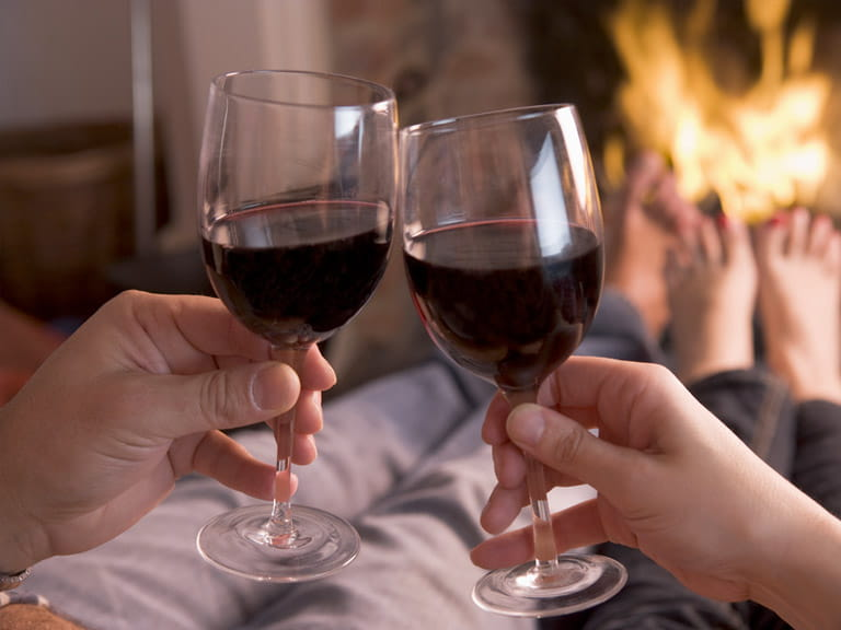 Couple toasting with wine in front of a roaring fire