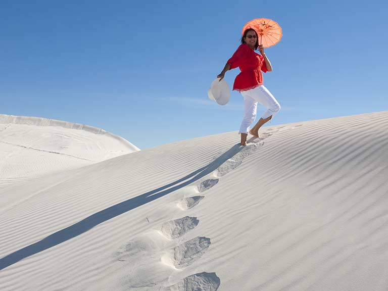 An older woman walks across the sand on her solo holiday