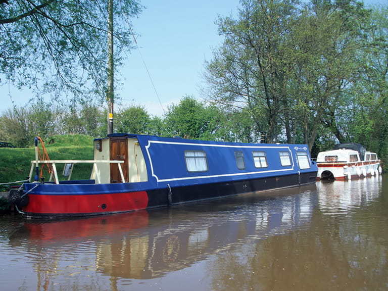 A blue narrow boat on the Brecon Canal