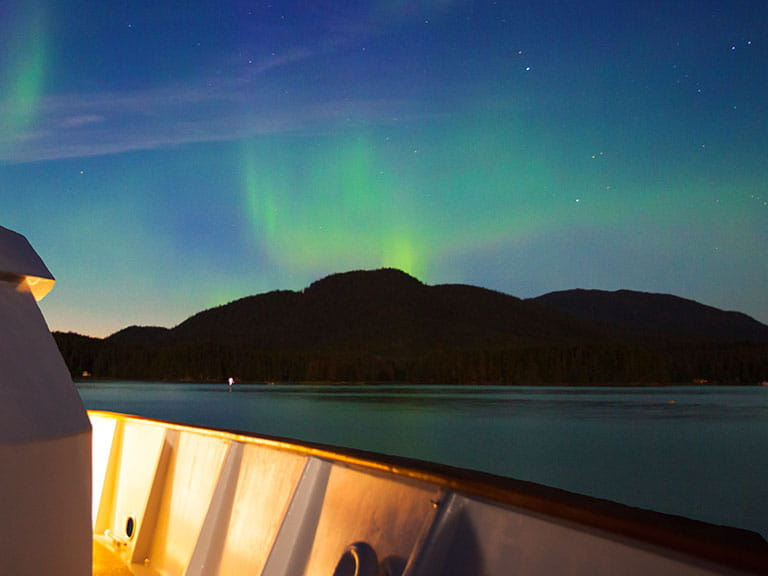 The northern lights in the sky over a cruise ship's deck