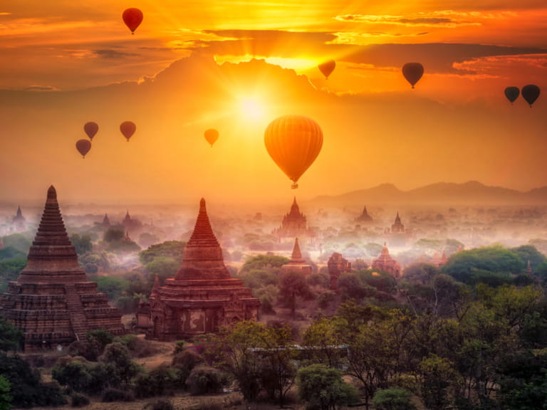 Hot air balloons over plain of Bagan in misty morning, Myanmar.=