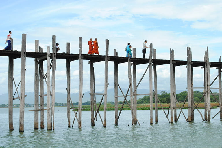 A bridge over the Ayeyarwady River with monks crossing=