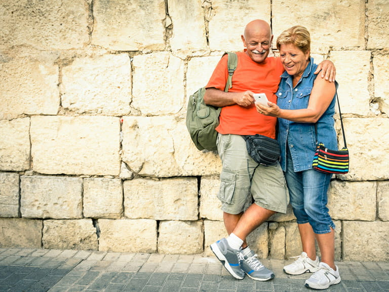 Senior couple looking up travel advice on holiday