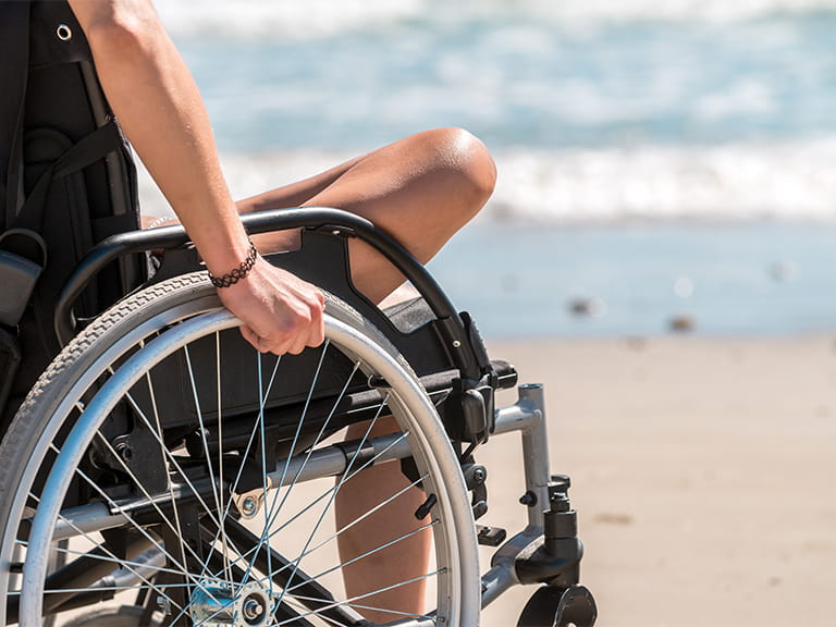 Woman in a wheelchair on a beach