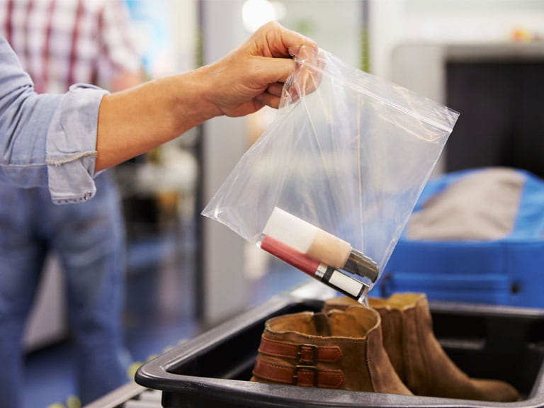 Woman sorting her liquids into a plastic bag at security