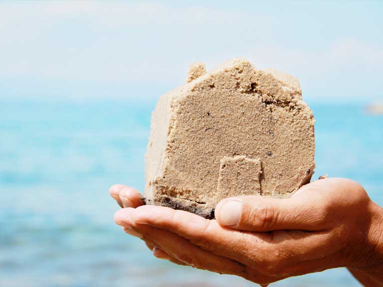 Sand house crumbling in a hand