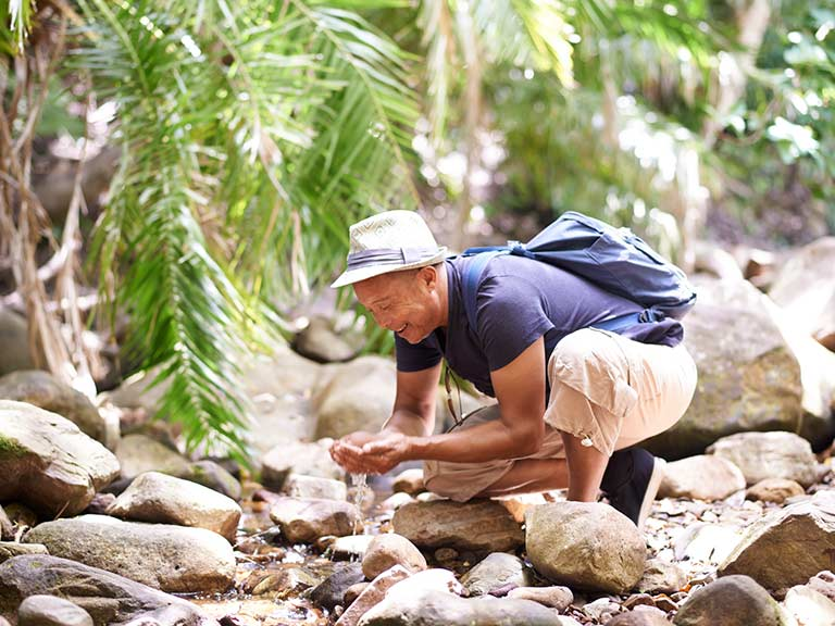 An older man drinks from a stream whilst travelling