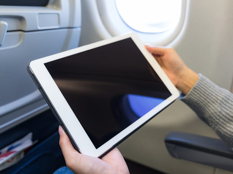 Woman holding tablet on an aeroplane