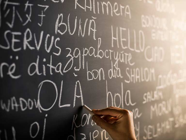 A blackboard with foreign language phrases to represent learning