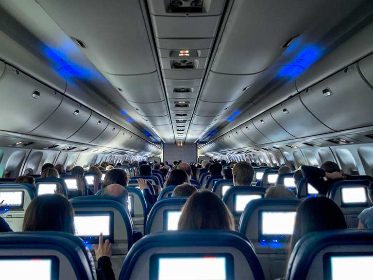 A aircraft cabin full of people watching their seat back screens during a long haul flight