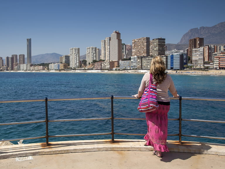 female gazes over sea and beach towards Playa de Levante, Benidorm, Spain