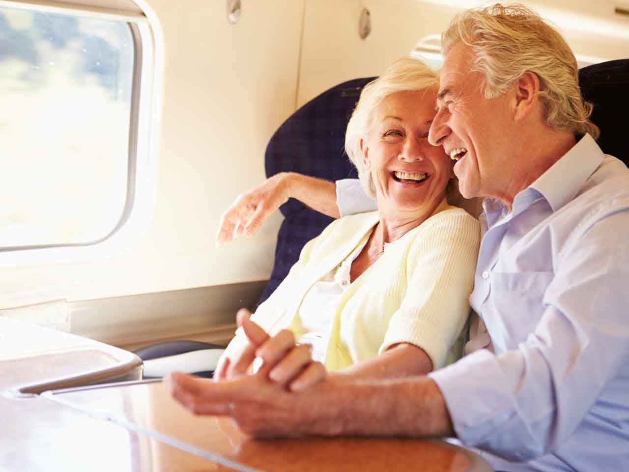 Happy senior couple travelling on a train
