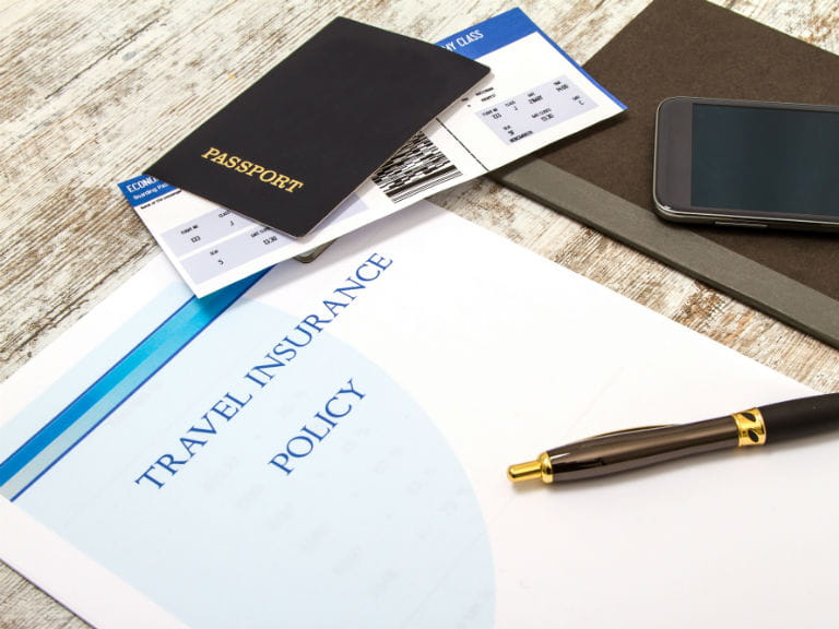 A passport, plane ticket, smartphone and travel insurance policy laying on a desk