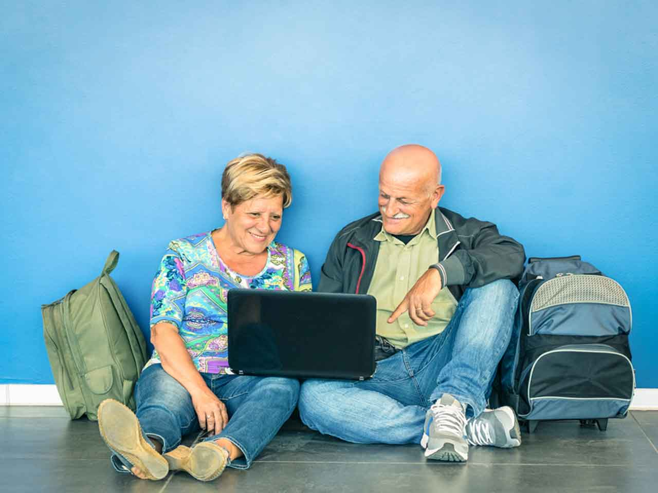 Over 50s at an airport gathering travel tips on a laptop