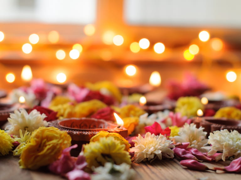 Diwali Candles and Oil Lamps with flowers on a wooden background