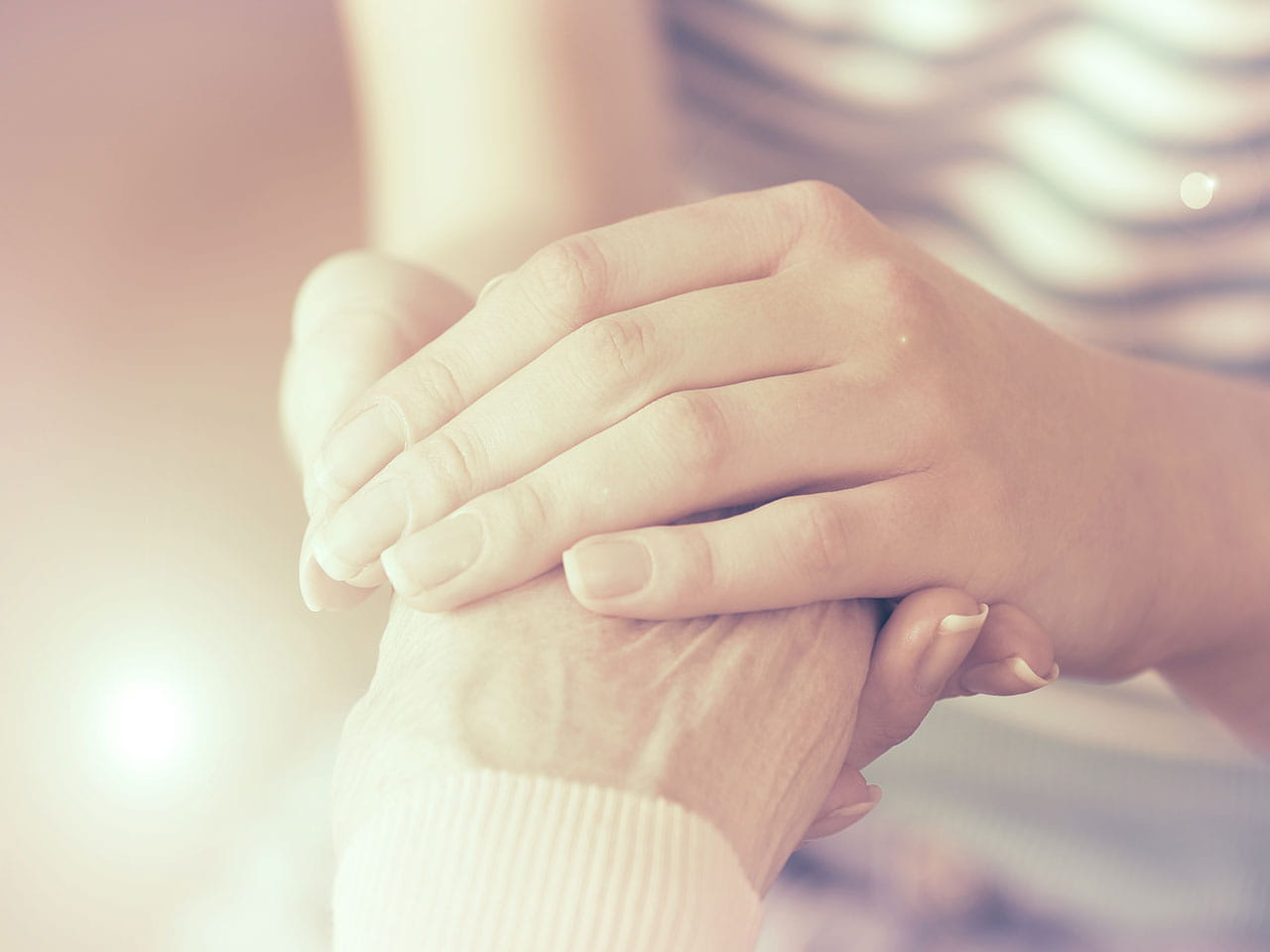 Hands holding older hands with care