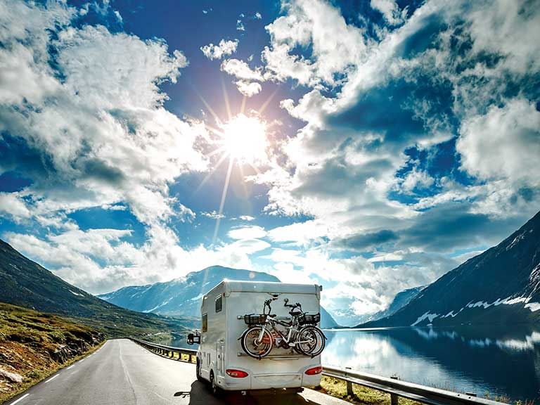 A caravan drives past a lake towards the sun