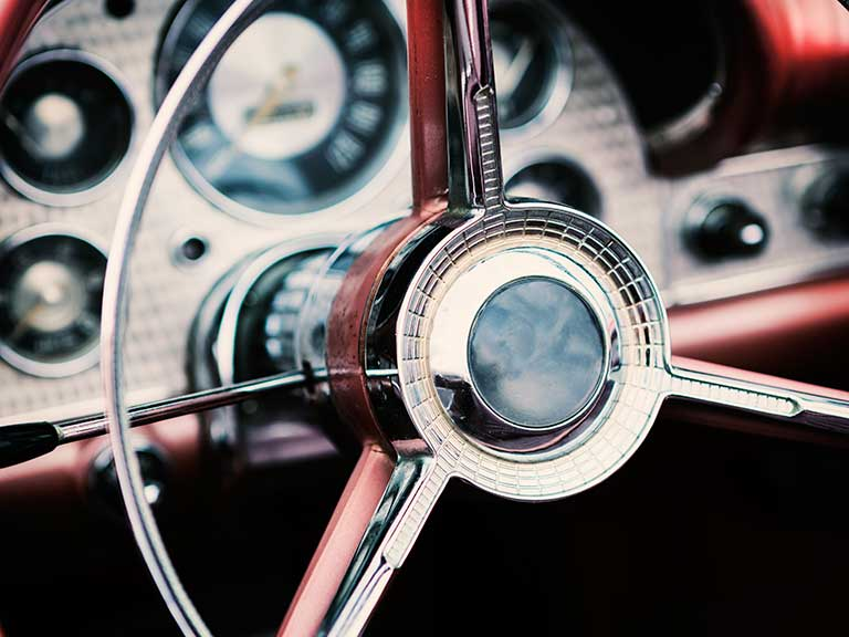A steering wheel of a traditional classic car
