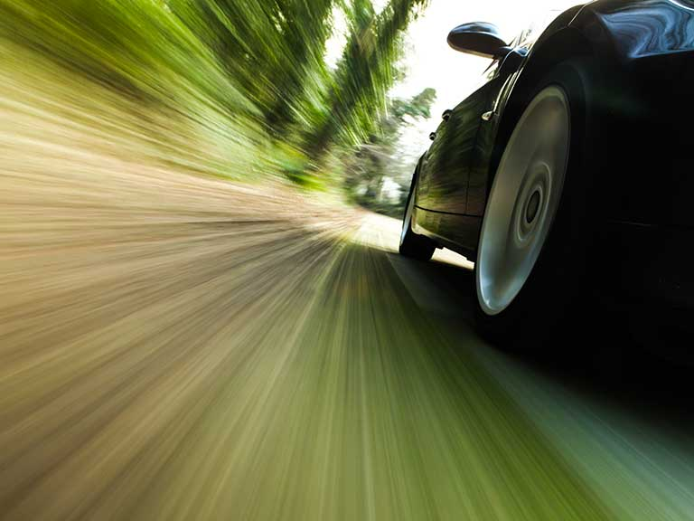 A car speeds along a country road, risking being hit by the speeding fine rise