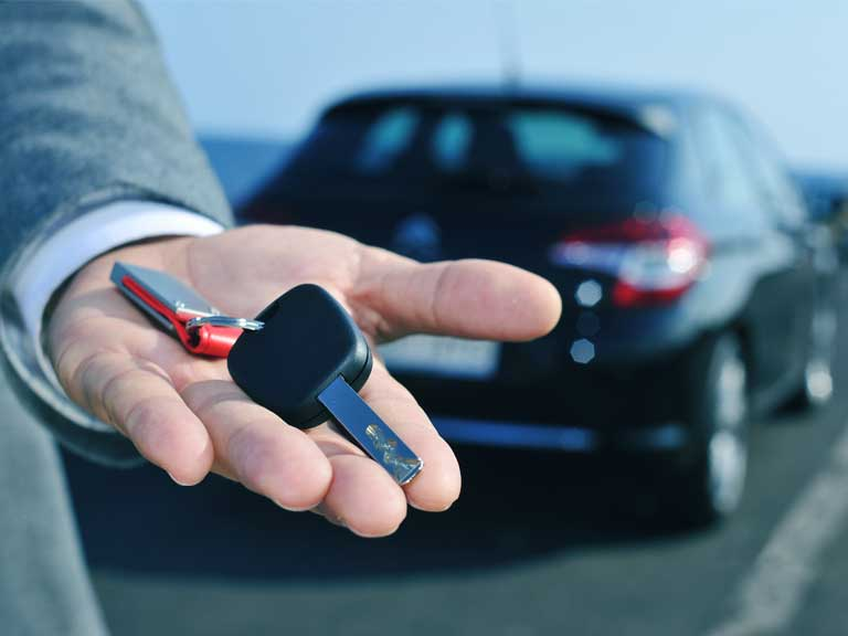 Car rental salesman handing over a hire car key