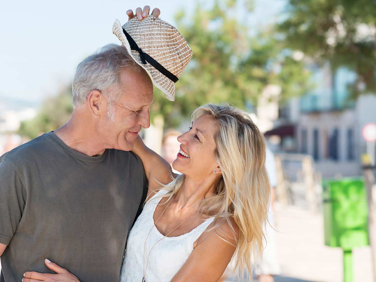 Mature couple messing about with a hat