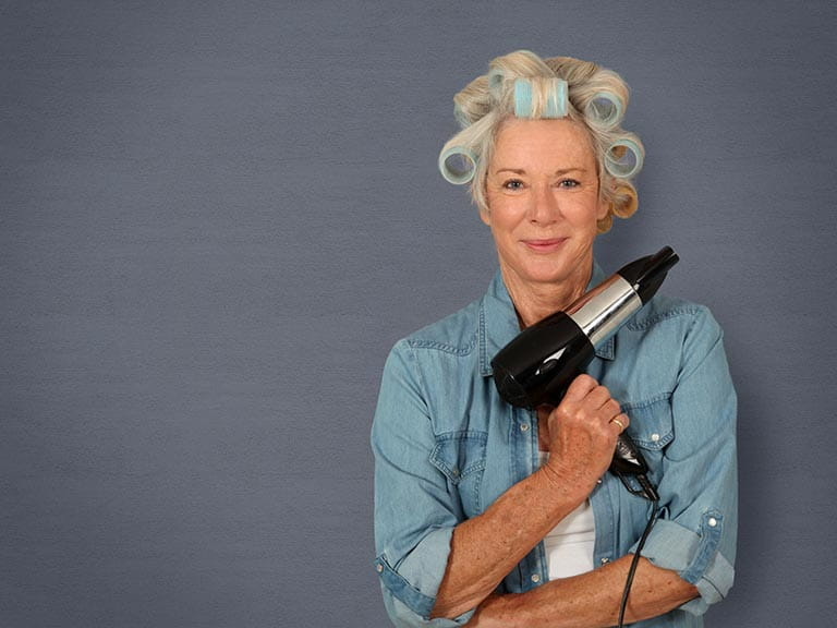 Mature lady thickening hair with rollers and hairdyer