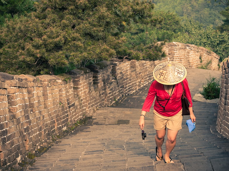 Solo travel lady walking along the Great Wall of China
