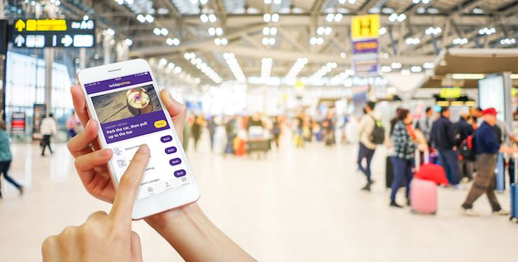 Hands holding mobile phone in airport using Holiday Extras app